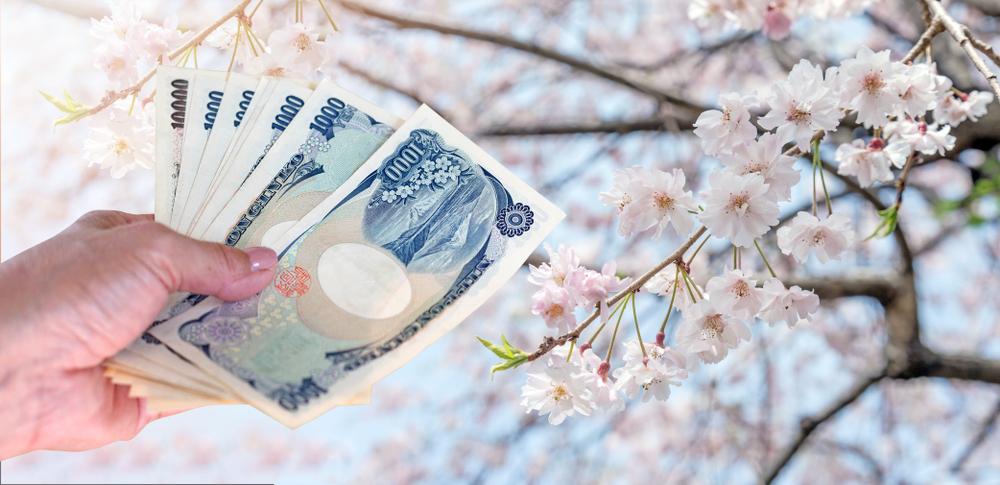 money in hand in front of sakura blossoms